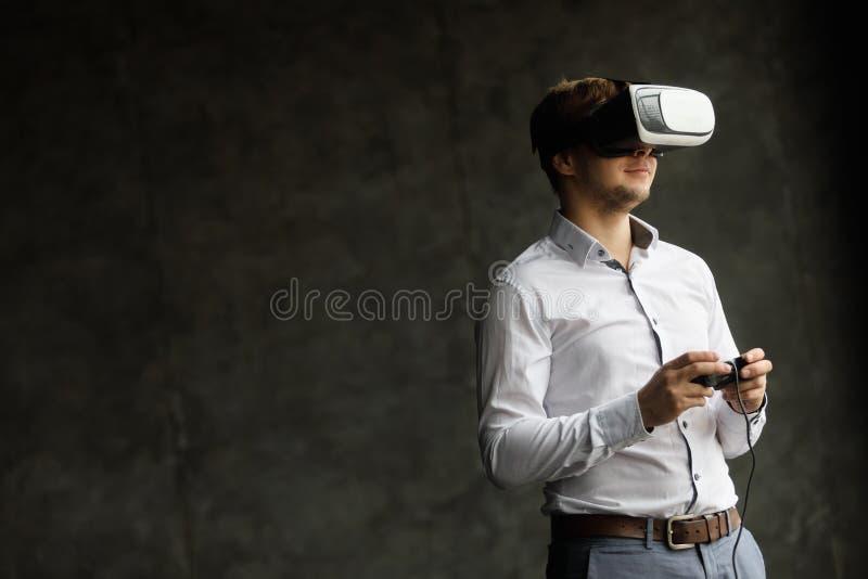 O projeto dos auriculares de VR é genérico e nenhuns logotipos, homem que veste os óculos de proteção da realidade virtual que ol fotografia de stock