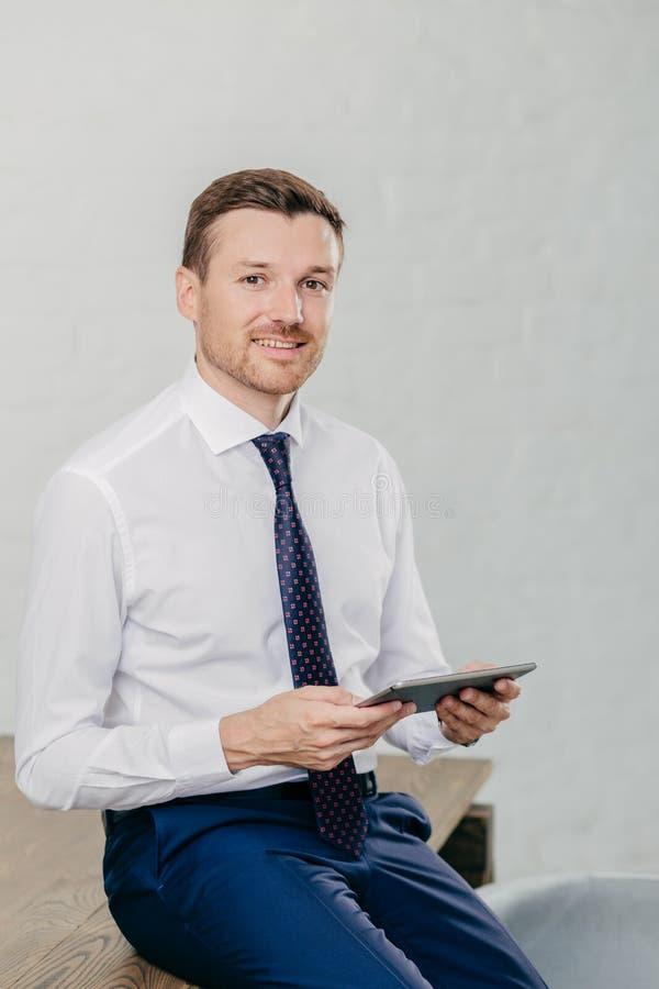 O proprietário bem sucedido da empresa financeira veste a roupa elegante, lê a notificação ou os chatts com os amigos na almofada foto de stock royalty free