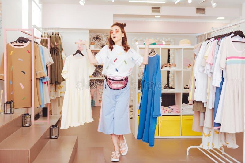 O proprietário novo da sala de exposições nova que pendura vestidos novos na roupa submete foto de stock royalty free