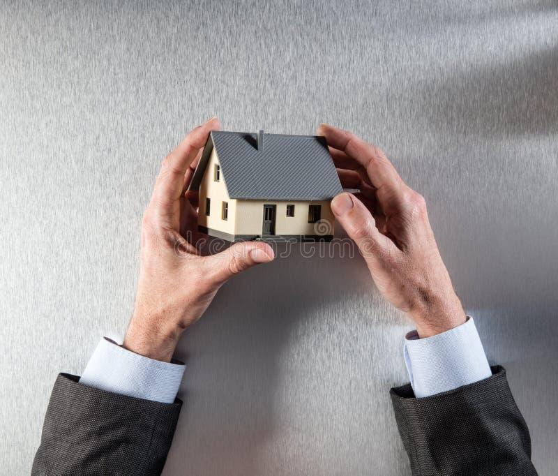 O proprietário novo entrega o pensamento sobre a casa para a avaliação da casa imagens de stock