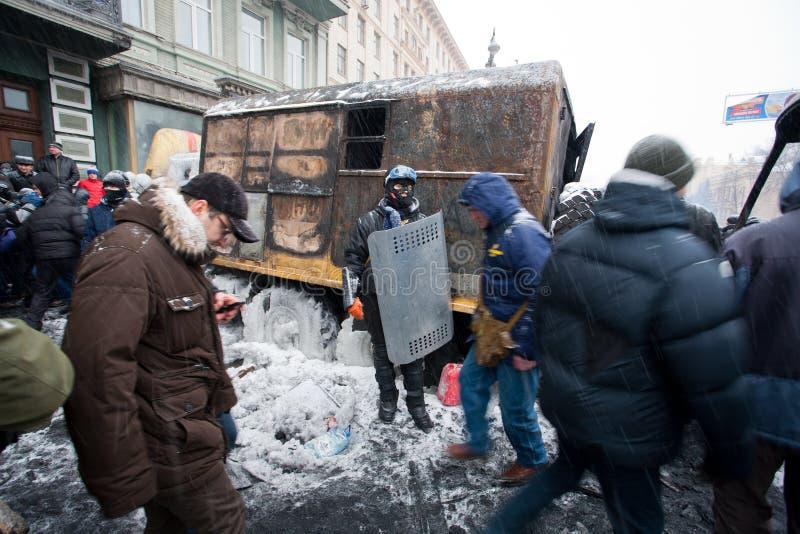 O protestador ativo com protetor e máscara está perto do automóvel militar queimado na rua do inverno durante o motim antigovernam imagens de stock royalty free