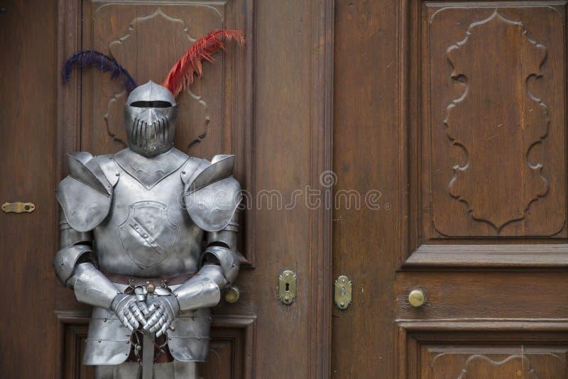 O protetor - cavaleiro medieval blindado que está na frente de uma porta velha fotos de stock