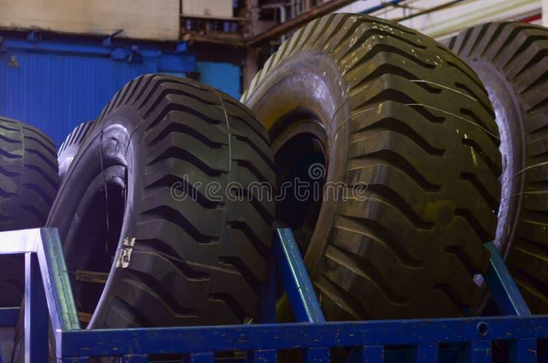 O protetor de uma grande roda de borracha Caminhões basculantes enormes da carreira do pneu de borracha, caminhões de mineração d fotos de stock