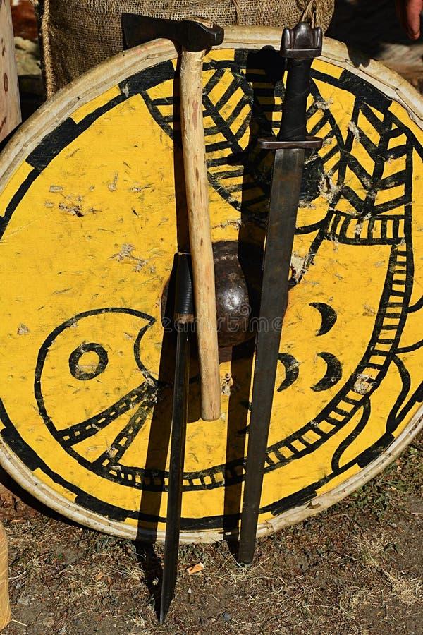 O protetor redondo medieval amarelo decorativo com pintura do pássaro, uma entregou a espada, o machado leve da batalha e o mache fotografia de stock royalty free