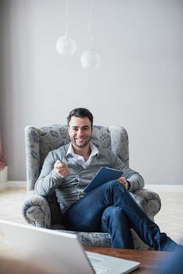 O psicólogo considerável está fazendo as anotações que sentam-se em seu escritório fotos de stock