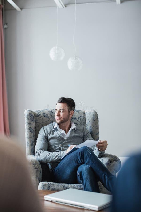 O psicólogo considerável está fazendo as anotações que sentam-se em seu escritório imagens de stock royalty free