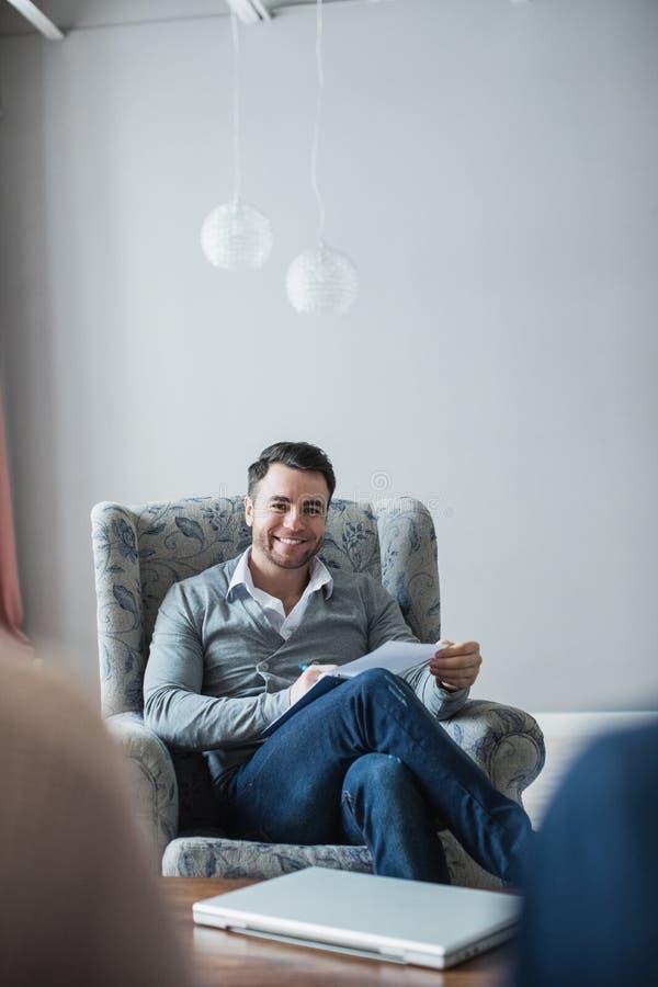 O psicólogo considerável está fazendo as anotações que sentam-se em seu escritório imagens de stock