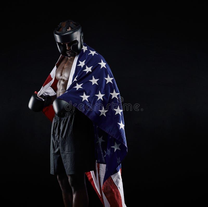 O pugilista africano com a bandeira drapejou em torno de seu corpo imagens de stock