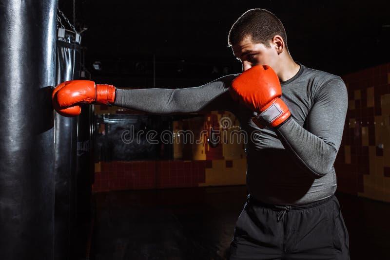 O pugilista bate um saco da velocidade no gym, treinando choque imagens de stock royalty free