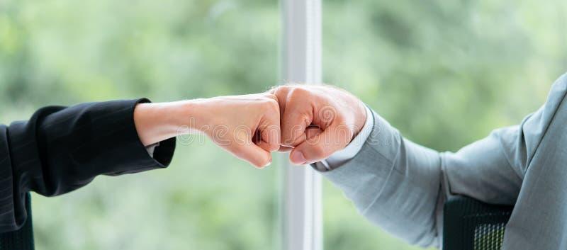 O punho do negócio do homem e da mulher de negócio colide a mão junto f imagens de stock royalty free