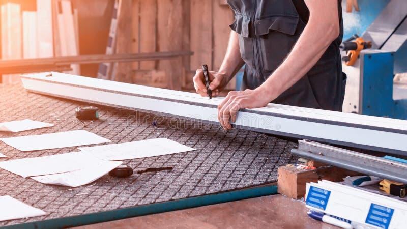 O pvc das janelas da produção, um homem escreve nas dimensões plásticas do perfil, close-up, pvc, escreve um marcador, braço foto de stock