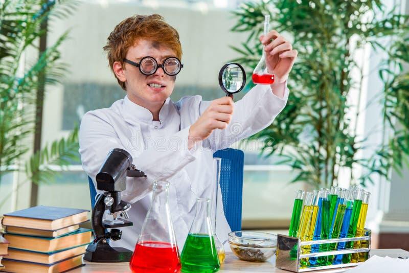 O químico louco novo que trabalha no laboratório foto de stock royalty free