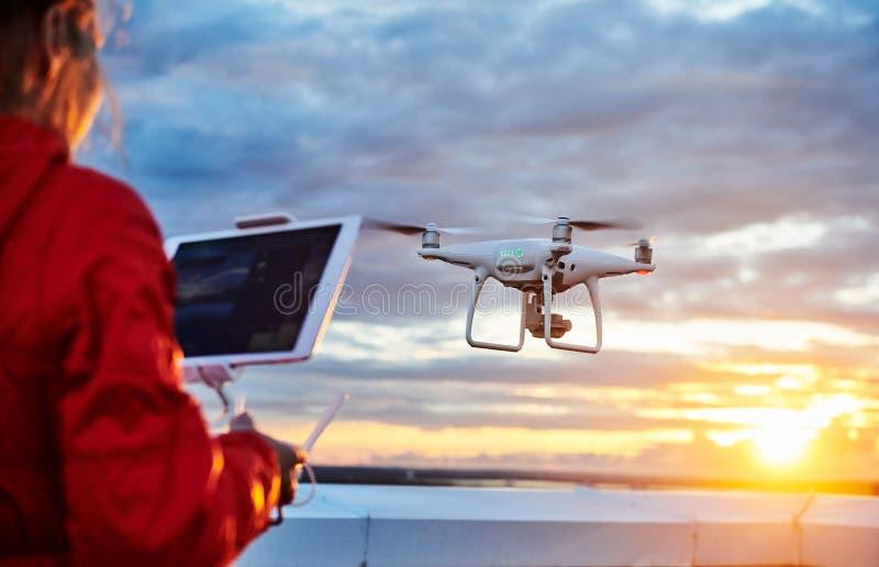 O quadcopter do zangão com câmara digital operou-se pela mulher no por do sol fotografia de stock royalty free