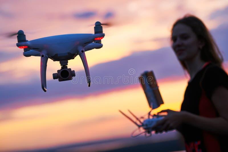 O quadcopter do zangão com câmara digital operou-se pela mulher no por do sol foto de stock