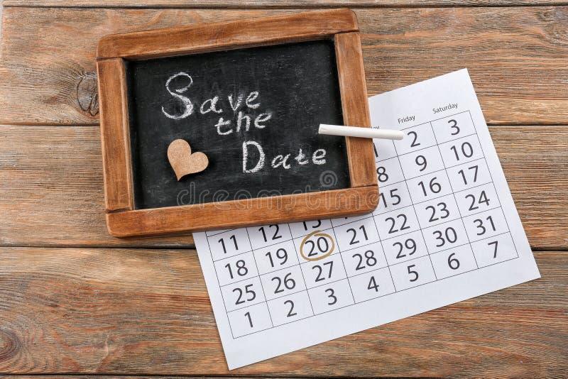 O quadro com inscrição salvar a data e o calendário na tabela de madeira foto de stock royalty free