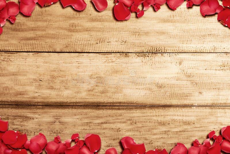 O quadro das pétalas de rosa vermelha com fundo de mesa de madeira imagem de stock royalty free