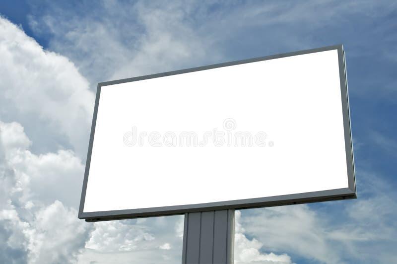 O quadro de avisos em branco sobre o céu nebuloso azul, apenas adiciona seu texto fotos de stock royalty free