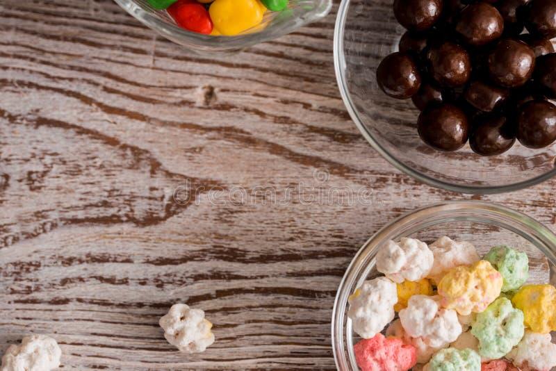 O quadro de doces sortidos brilhantes coloridos em umas bacias e uns frascos, uns bastões de doces e um arco-íris coloriu pirulit fotos de stock