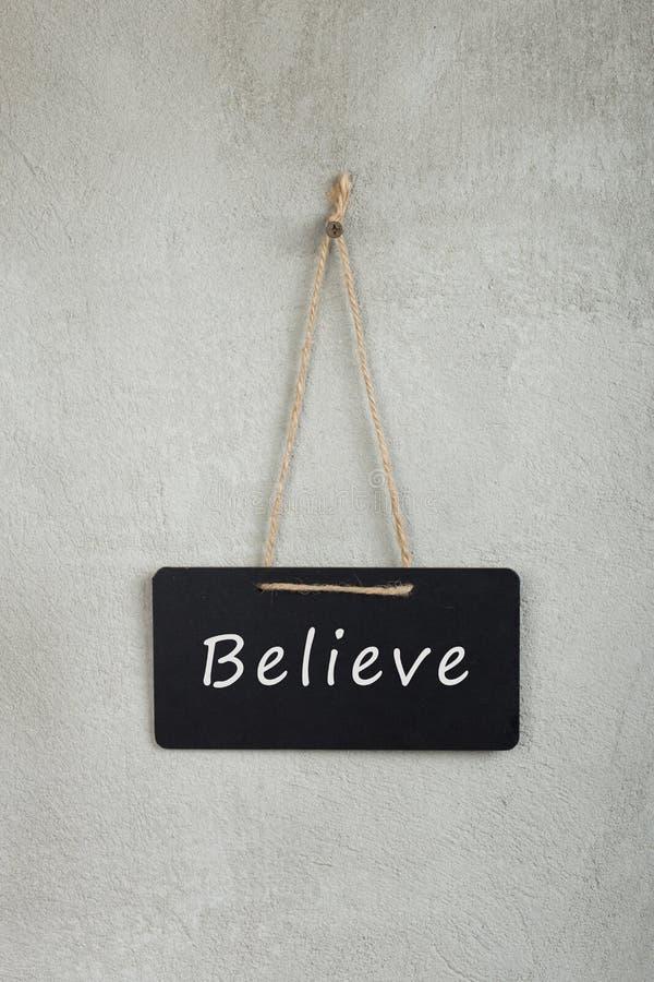 O quadro de mensagens preto, quadro-negro, quadro com texto acredita na parede cinzenta do cimento imagem de stock royalty free