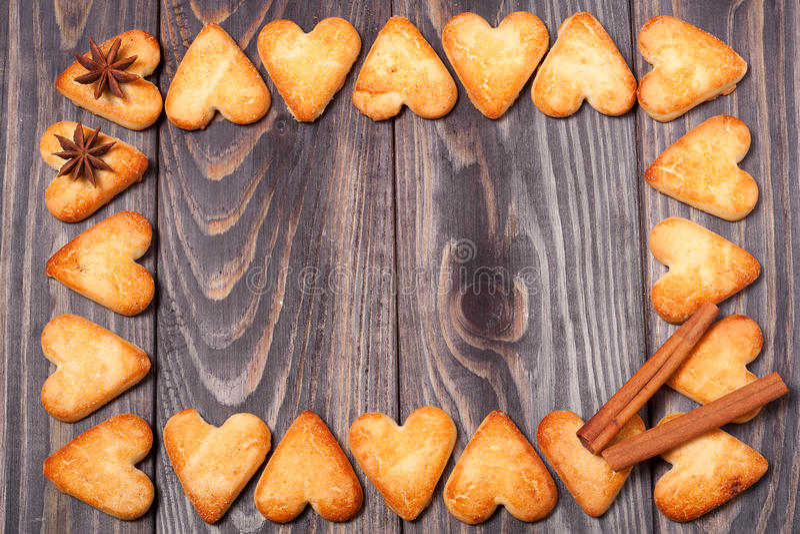O quadro do coração deu forma a cookies na tabela de madeira imagens de stock royalty free