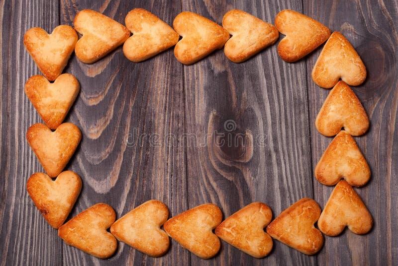 O quadro do coração deu forma a cookies na tabela de madeira imagem de stock royalty free