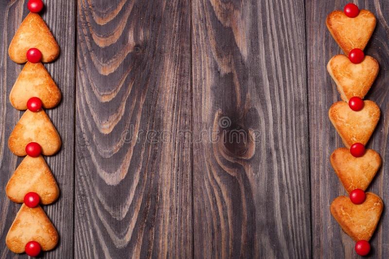 O quadro do coração deu forma a cookies na tabela de madeira imagem de stock