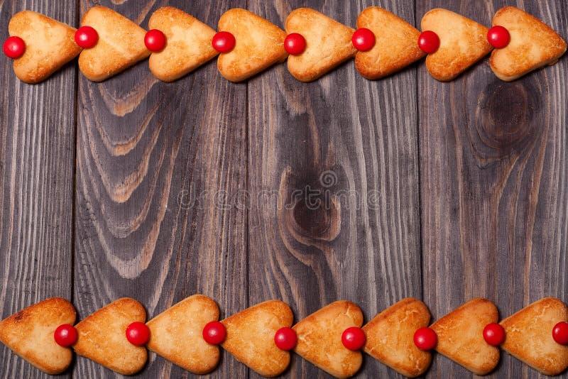 O quadro do coração deu forma a cookies na tabela de madeira fotografia de stock