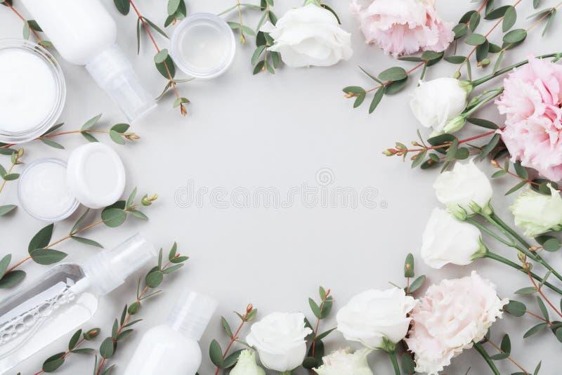 O quadro do cosmético natural orgânico decorou flores e o eucalipto verde sae na opinião de tampo da mesa Configuração lisa imagem de stock