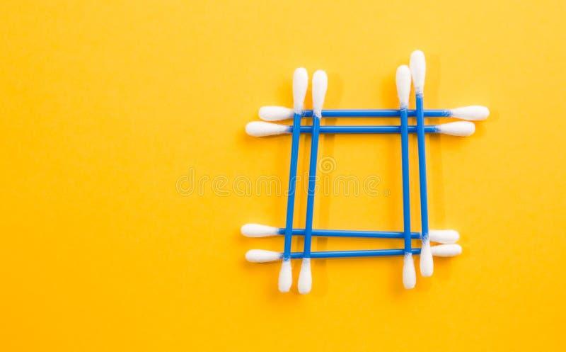 O quadro feito do algodão azul brota no fundo amarelo fotos de stock