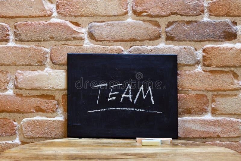O quadro-negro com a equipe da palavra afoga-se à mão na tabela de madeira no fundo da parede de tijolo fotografia de stock