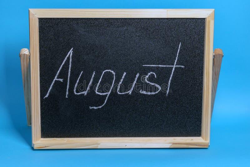 O quadro-negro com a palavra riscou august no fundo azul imagens de stock