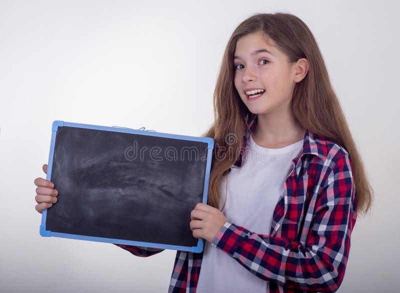 O quadro-negro da terra arrendada da moça com espaço da cópia e anuncia algo imagens de stock royalty free
