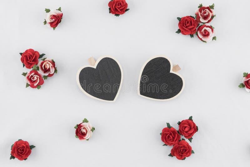 O quadro-negro minúsculo da forma do coração decora com as flores de papel da rosa do vermelho fotos de stock