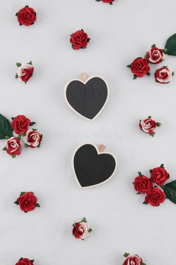 O quadro-negro minúsculo da forma do coração decora com as flores de papel da rosa do vermelho fotografia de stock royalty free