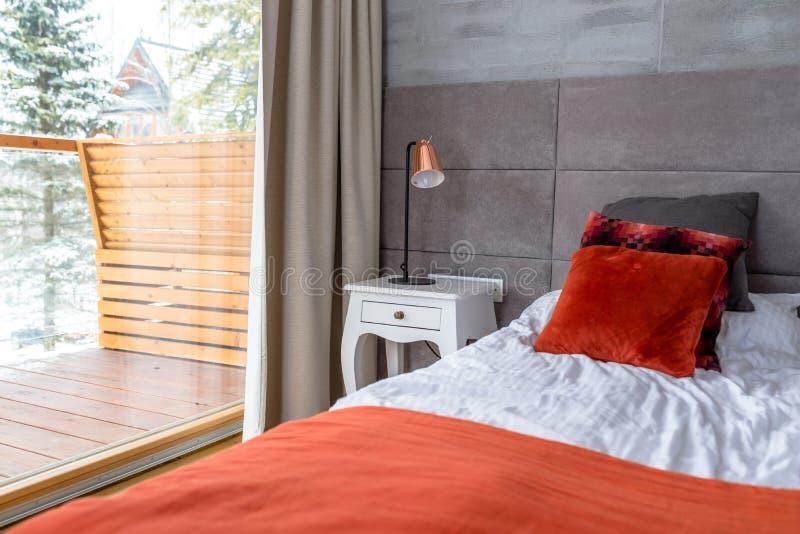 O quarto com uma grande cama, descansos alaranjados arranjou em seguido, parede cobriu com o material cinzento, a tabela visível  imagem de stock