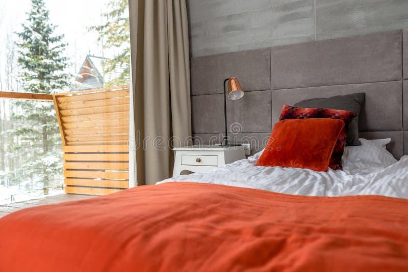 O quarto com uma grande cama, descansos alaranjados arranjou em seguido, parede cobriu com o material cinzento, a tabela visível  imagens de stock