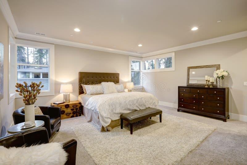 O quarto principal bege e marrom vangloria-se da cama de rainha adornada foto de stock royalty free