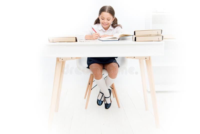O que deve estar a uma altura da tabela do estudo Estudante que faz trabalhos de casa na tabela Menina adorável do aluno que estu fotos de stock