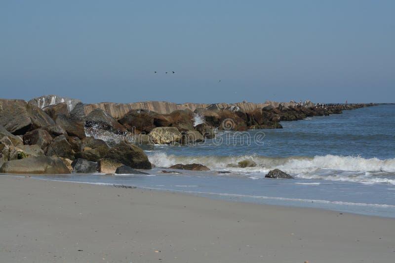 O quebra-mar do molhe na praia de Fernandina, parque estadual do rebitamento do forte, o Condado de Nassau, Florida EUA imagem de stock