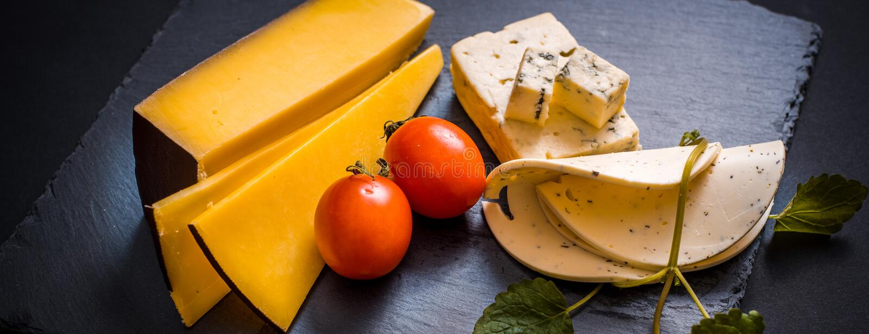 O queijo com molde, tomates de cereja, manjericão e melissa esverdeia, pimenta encarnado em uma bandeja de pedra em uma obscurida imagem de stock royalty free
