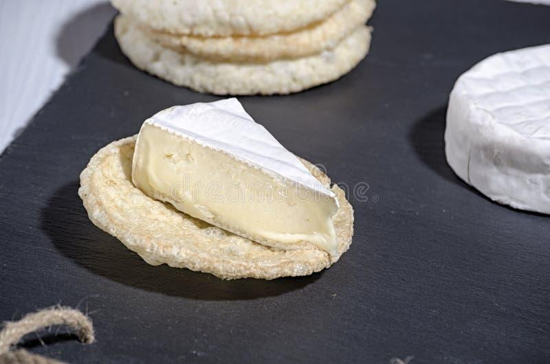 O queijo de famille do brie e os nacos redondos pequenos encontram-se em uma placa da ardósia em um fundo de madeira branco, quei fotografia de stock