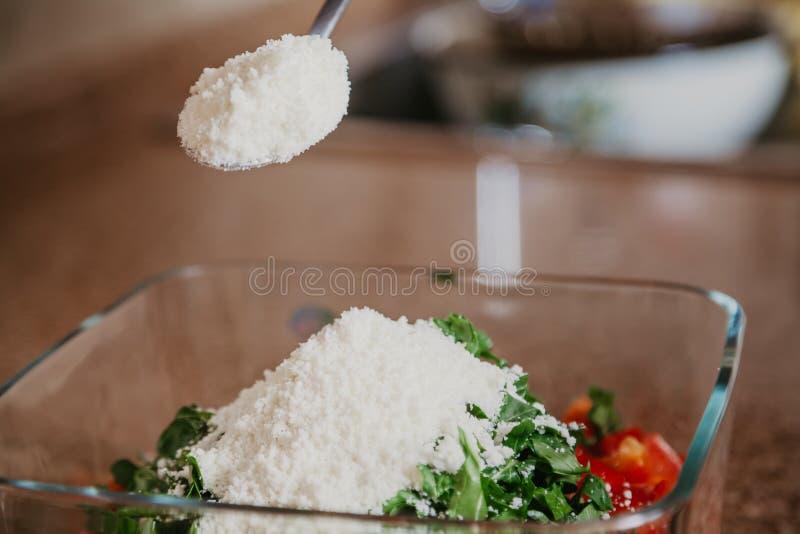 O queijo raspado ? coberto na salada no recipiente de vidro quadrado fotografia de stock
