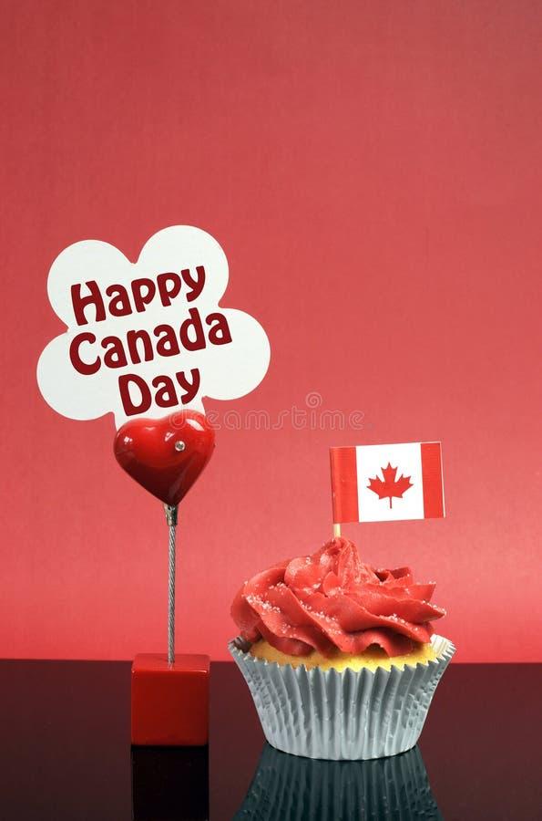 O queque canadense com bandeira da folha de bordo e o dia feliz de Canadá assinam imagens de stock royalty free