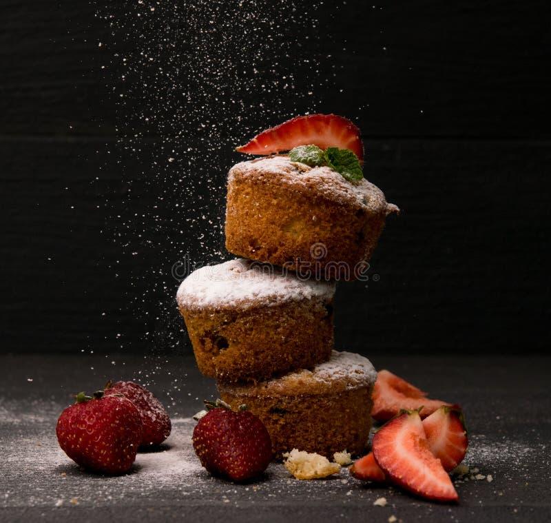 O queque do bolo do pó da neve do açúcar do blackground do queque da morango cozeu fotos de stock royalty free