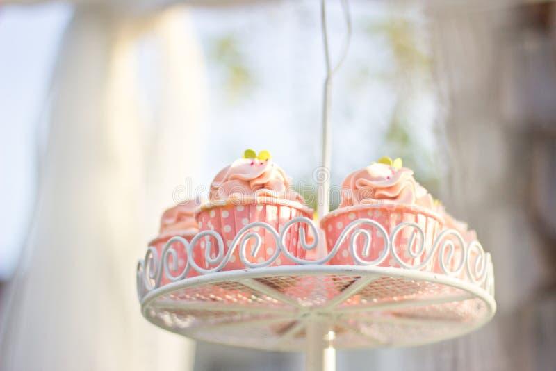 O queque do casamento tem a cor cor-de-rosa em prateleiras foto de stock royalty free