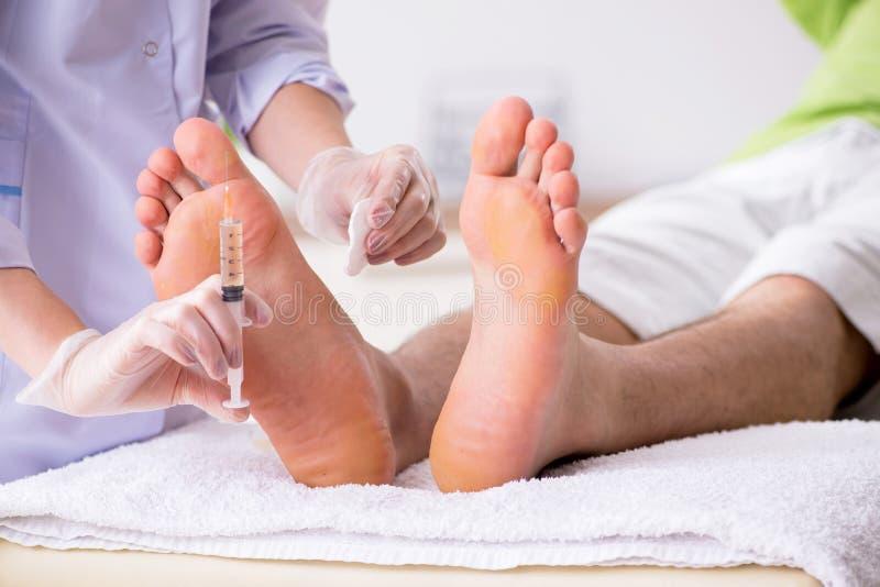 O quiropodista que trata os pés durante o procedimento fotos de stock