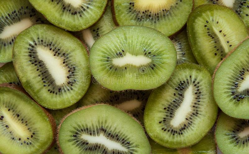 O quivi cortou o fundo verde Lotes de frutos tropicais verdes Corte o quivi em partes fotos de stock royalty free