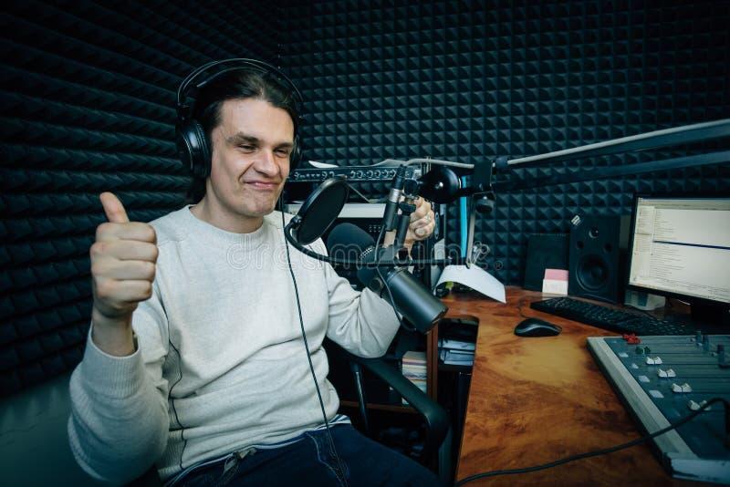 O rádio de fala de sorriso DJ mostra os polegares acima no estúdio de rádio fotos de stock royalty free
