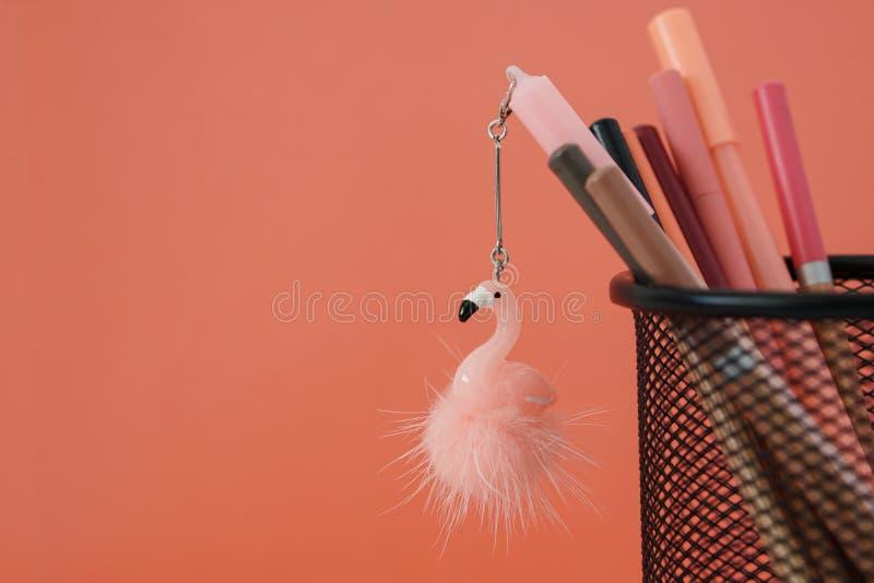 o r 与火鸟玩具和铅笔的笔在珊瑚色的背景的篮子与赠送阅本 库存照片