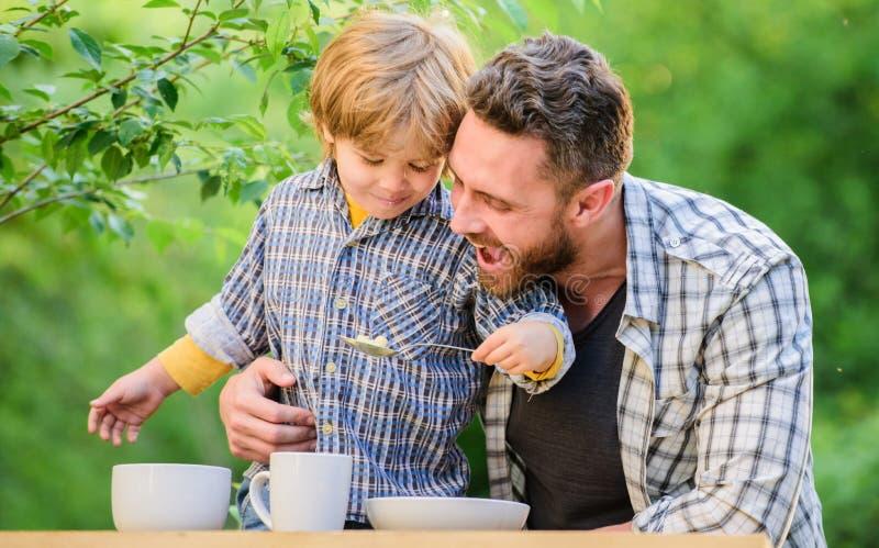 o r 有室外的爸爸的小男孩 健康食品和节食 o 儿子和 免版税图库摄影